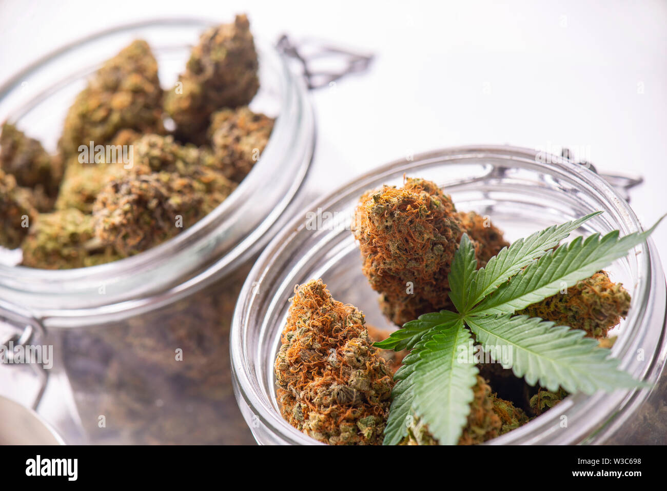 Detail of cannabis buds on clear glass jars isolated on white - medical marijuana dispensary concept Stock Photo