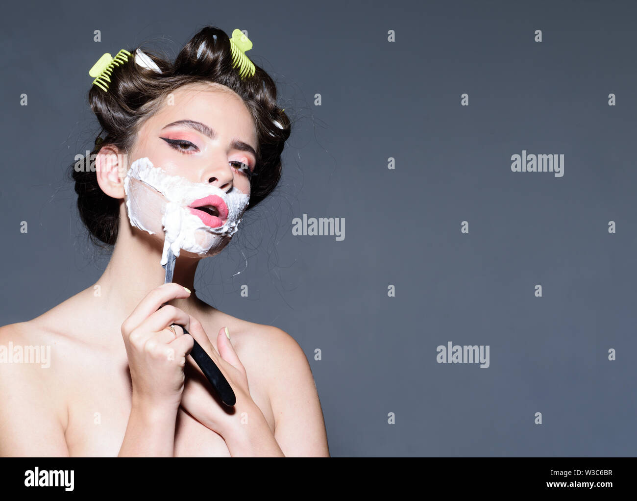morning grooming and skincare. pinup girl with fashion hair. retro woman shaving with foam and razor blade. pin up woman with trendy makeup. pretty gi - Stock Image