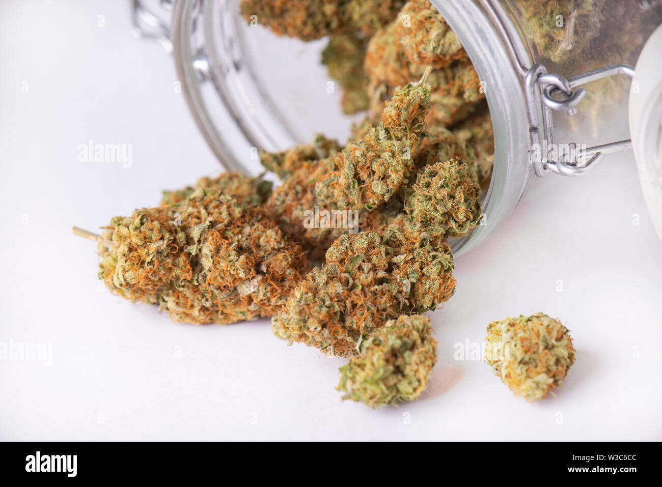 Detail of cannabis buds on clear glass jar isolated on white - medical marijuana dispensary concept Stock Photo