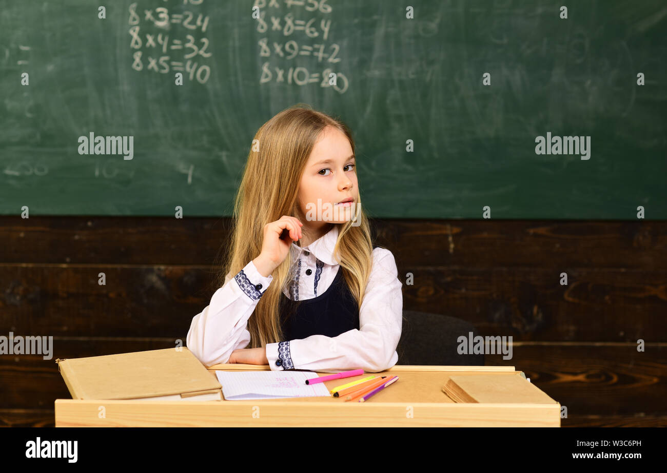 Attentive students writing something in their note pads while sitting at desks in the classroom. Lesson with qualified private tutor. Help with - Stock Image
