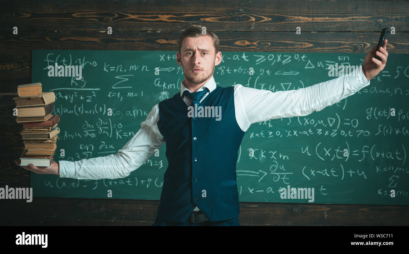 Man teacher balancing in hands pile of books and smartphone as analog and digital information storages. Teacher formal wear, chalkboard background - Stock Image