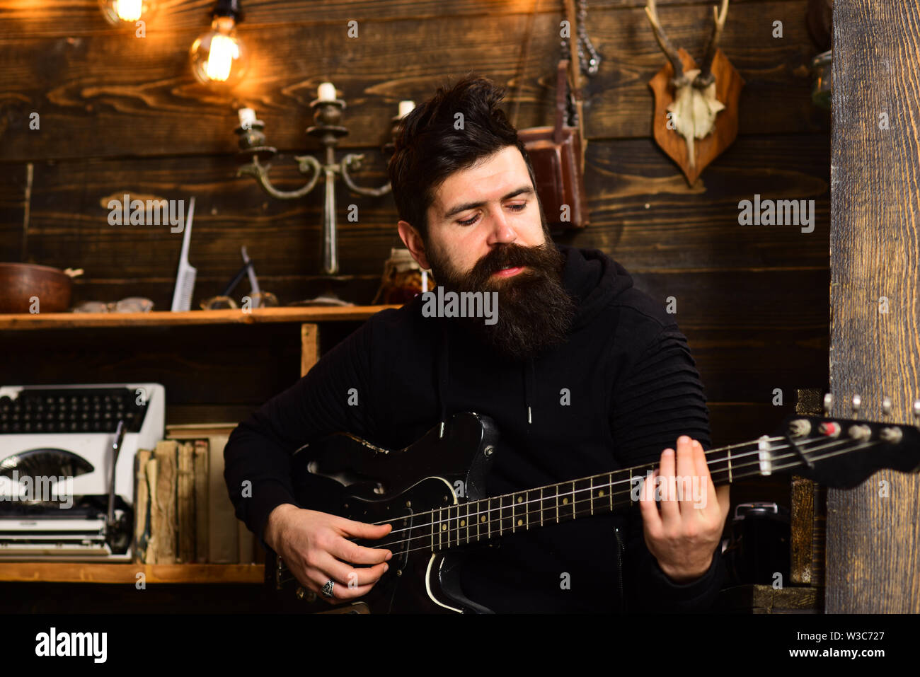 Man bearded musician enjoy evening rehearsing performance at home, wooden background. Boost your skills. Guy in cozy warm atmosphere learn new song Stock Photo