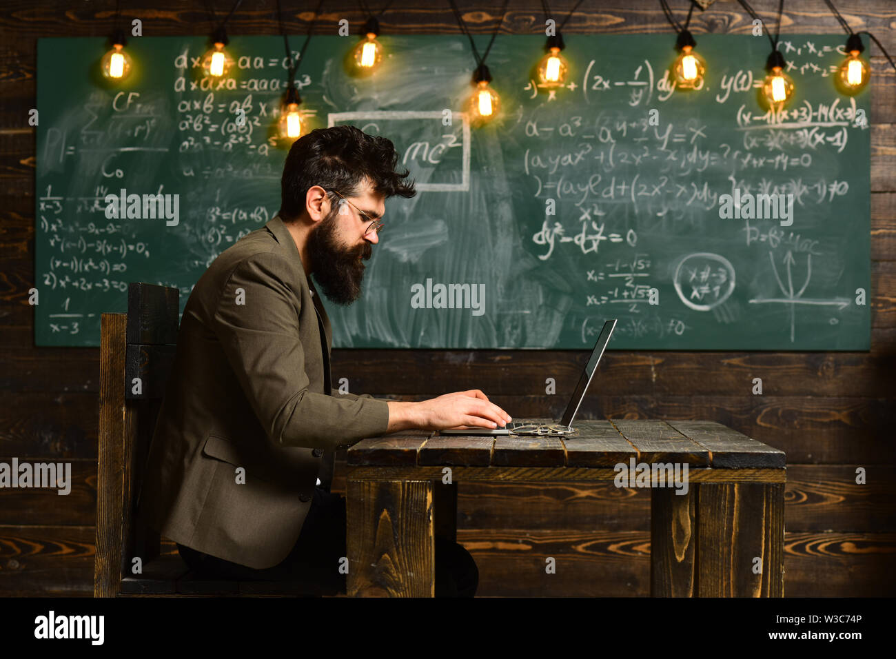 Modern teacher hipster writing on big blackboard with math formula, E-Learning concept with student holding his modern laptop computer, - Stock Image