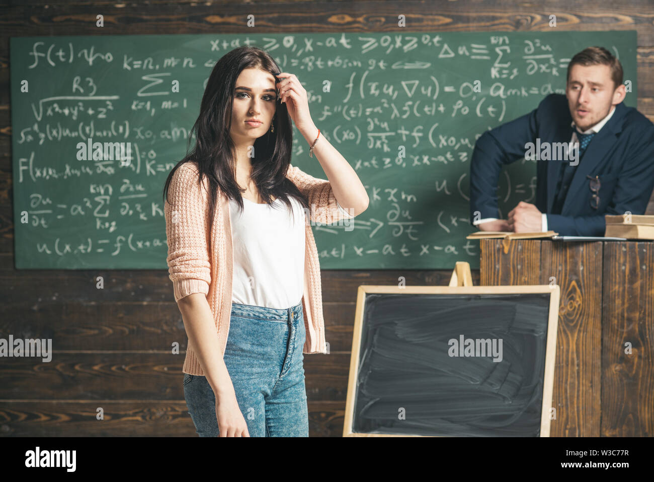 Young female student in pink cardigan and blue jeans standing in front of green board. Brunette teenage girl in the classroom listening to - Stock Image