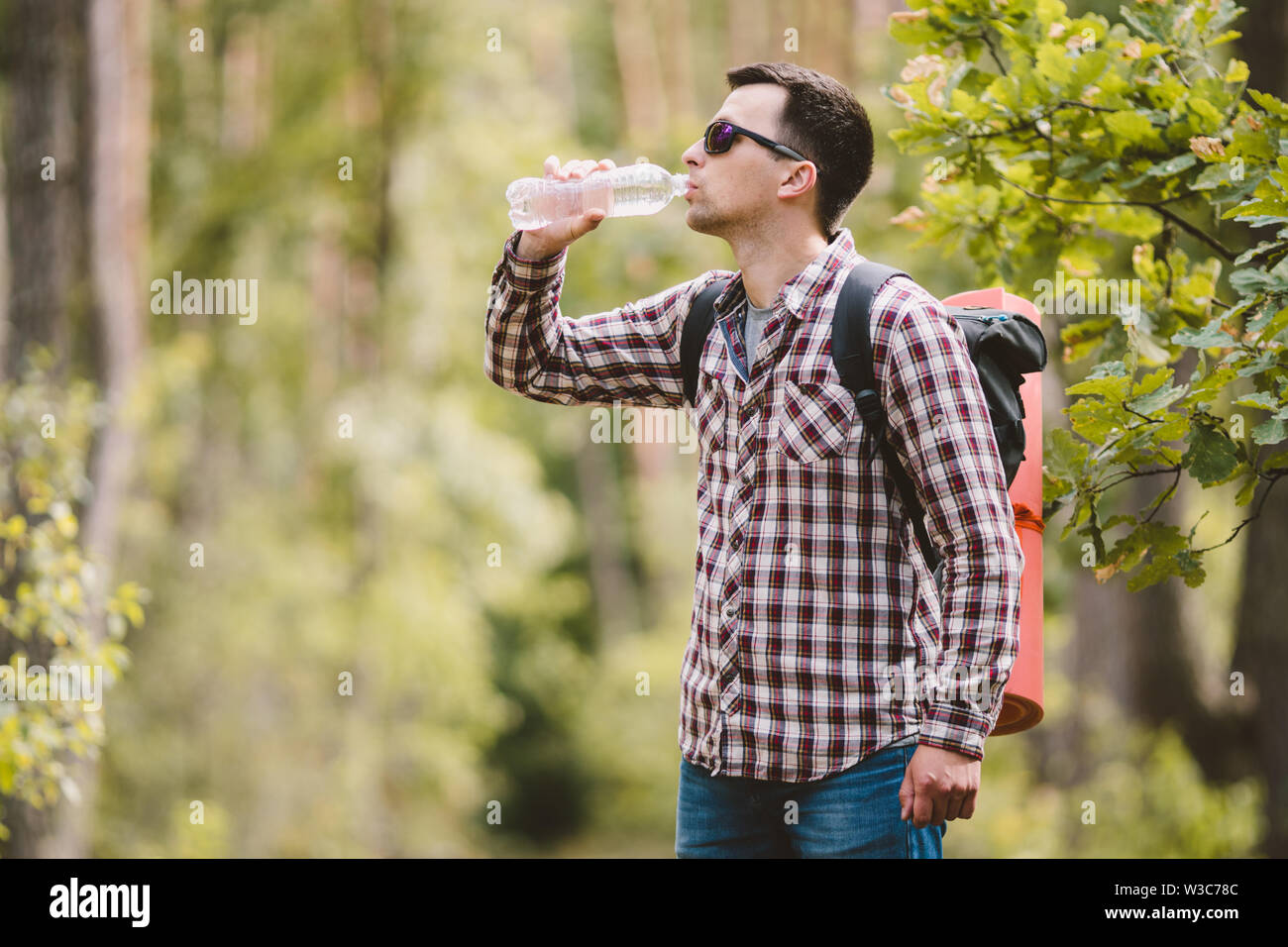 Hiker Drinking Water In Forest. Tired man drinking water from bottle in woodland. Handsome Traveler With Backpack And Flask In Forest. vacation, outdo - Stock Image