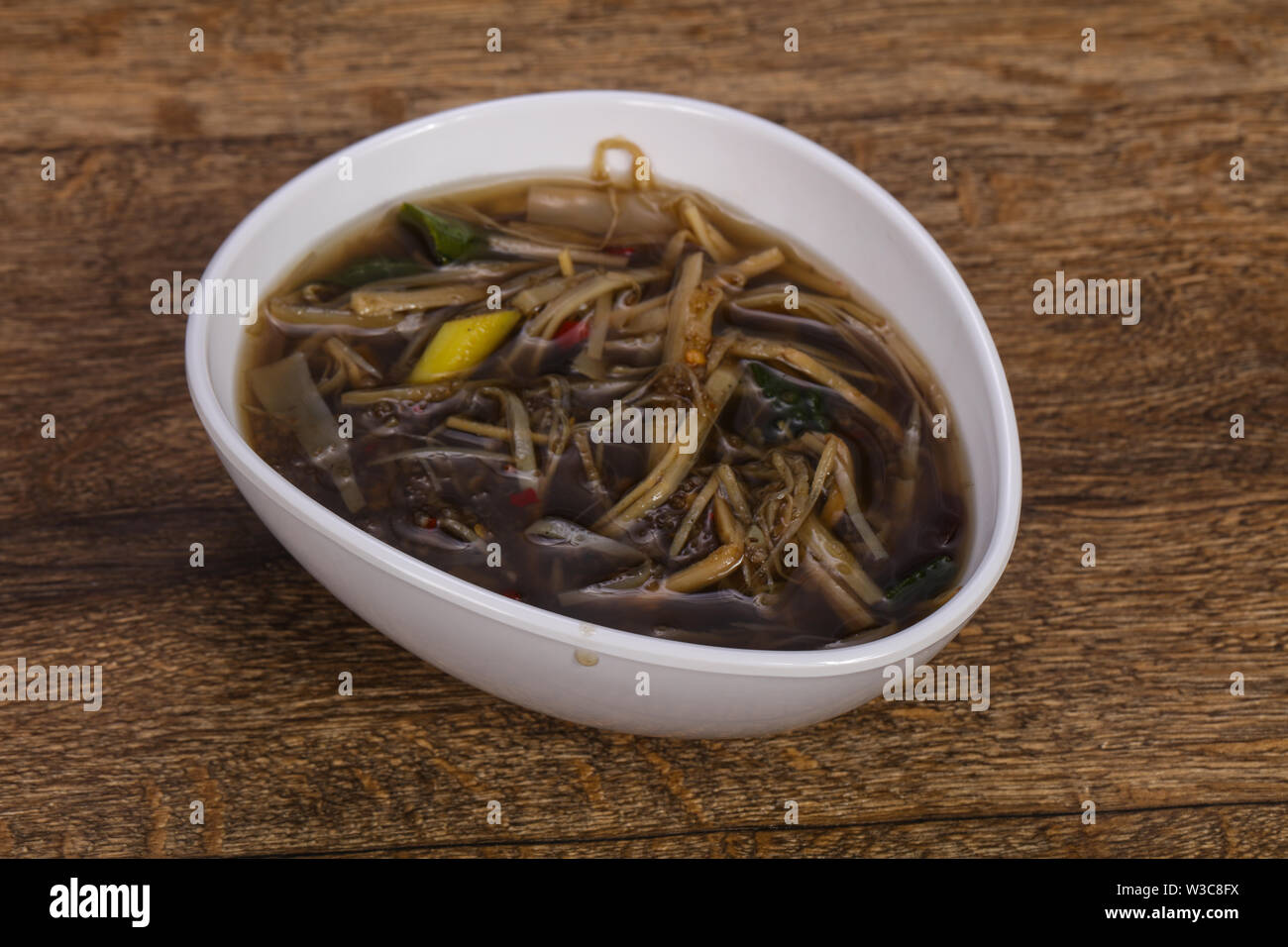 Thai style soup with meat, vegetables and mushrooms - Stock Image