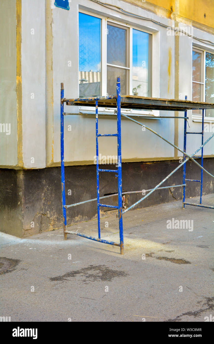 Outside repair and renovation of a apartment house using blue paint metal small scaffolding tower. Corner of an urban typical apartment building with - Stock Image