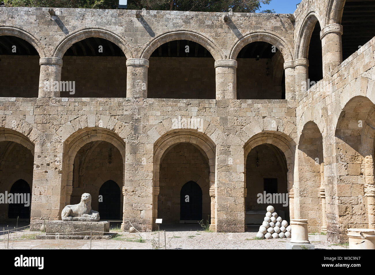 Rhodes Old City - Archaeological museum, old Hospital of the Knights. Courtyard surrounded by a galleries, lion statue and stacks of cannon balls. Dod - Stock Image
