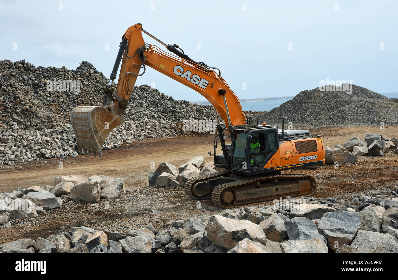 Digger moving large boulders on construction site. - Stock Image
