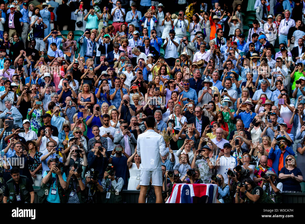 London, UK. 14th July 2019. Wimbledon Tennis Tournament, Day 13, mens singles final; Novak Djokovic (SER) has his photograph taken by photographers and the crowd with the Wimbledon mens singles final trophy Credit: Action Plus Sports Images/Alamy Live News Stock Photo