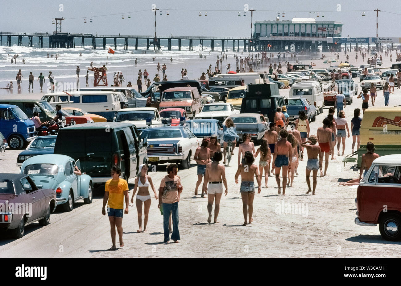 School holidays during Easter Week have long drawn crowds of teenagers to the beaches of Florida, USA, especially to places like Daytona Beach, photographed here in 1978, where motor vehicles can be driven and parked right on the hard-packed sand. Current rules now limit vehicles on the beach to specific areas between certain hours and a speed limit of 10 miles (16 kilometers) per hour. Also, there are traffic-free zones to protect sunbathing beachgoers from the cruising cars. When the tide is out, Daytona's 23-mile-long (37 kilometer) beach has plenty of room for a leisurely drive. - Stock Image