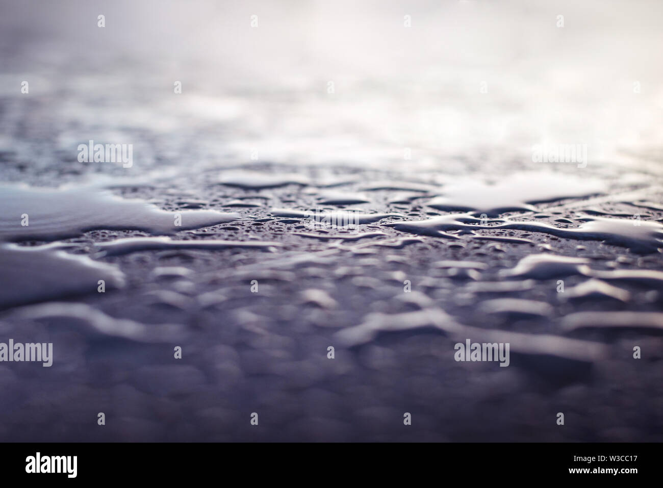 Water drops after the rain on the stone surface. - Stock Image