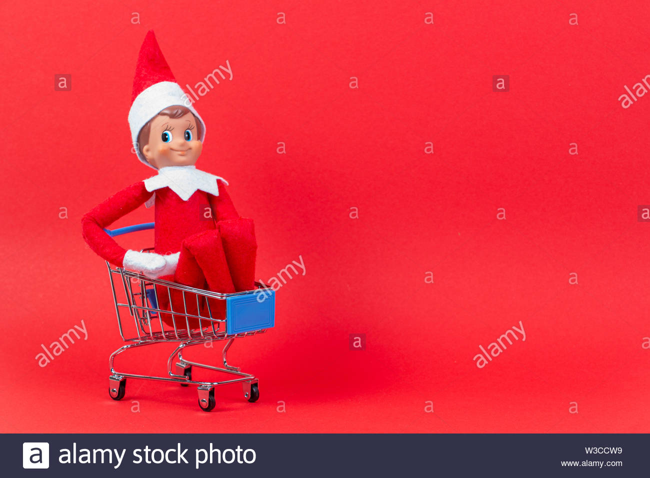 Christmas toy elf on shelf sitting in mini shopping cart on red background - Stock Image