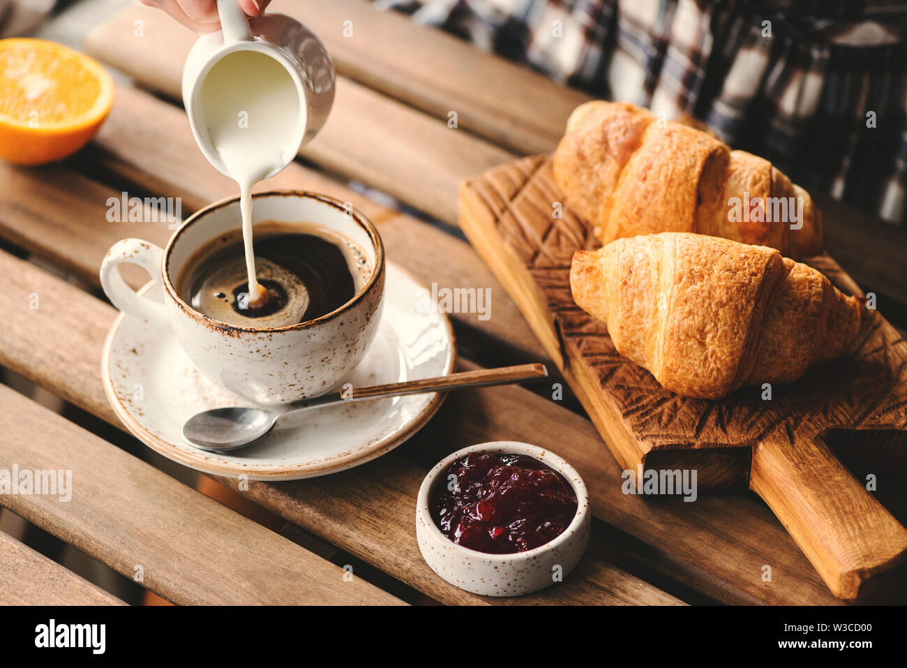 Pouring Cream Into Cup Of Black Coffee Tasty Breakfast Table Set With Croissants Jam And Coffee Stock Photo Alamy