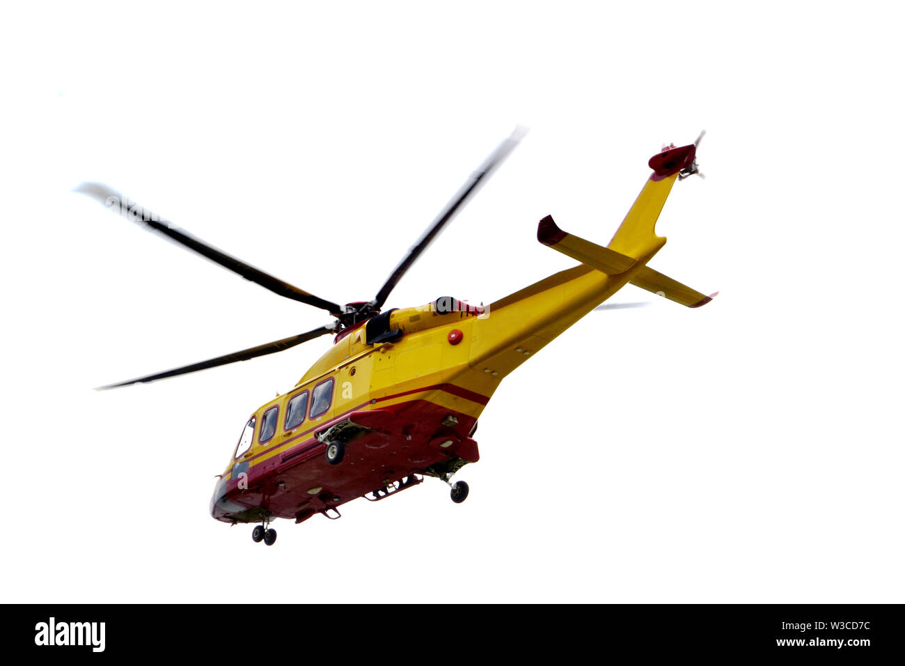 Side view to yellow emergency helicopter flying in the sky. Stock Photo
