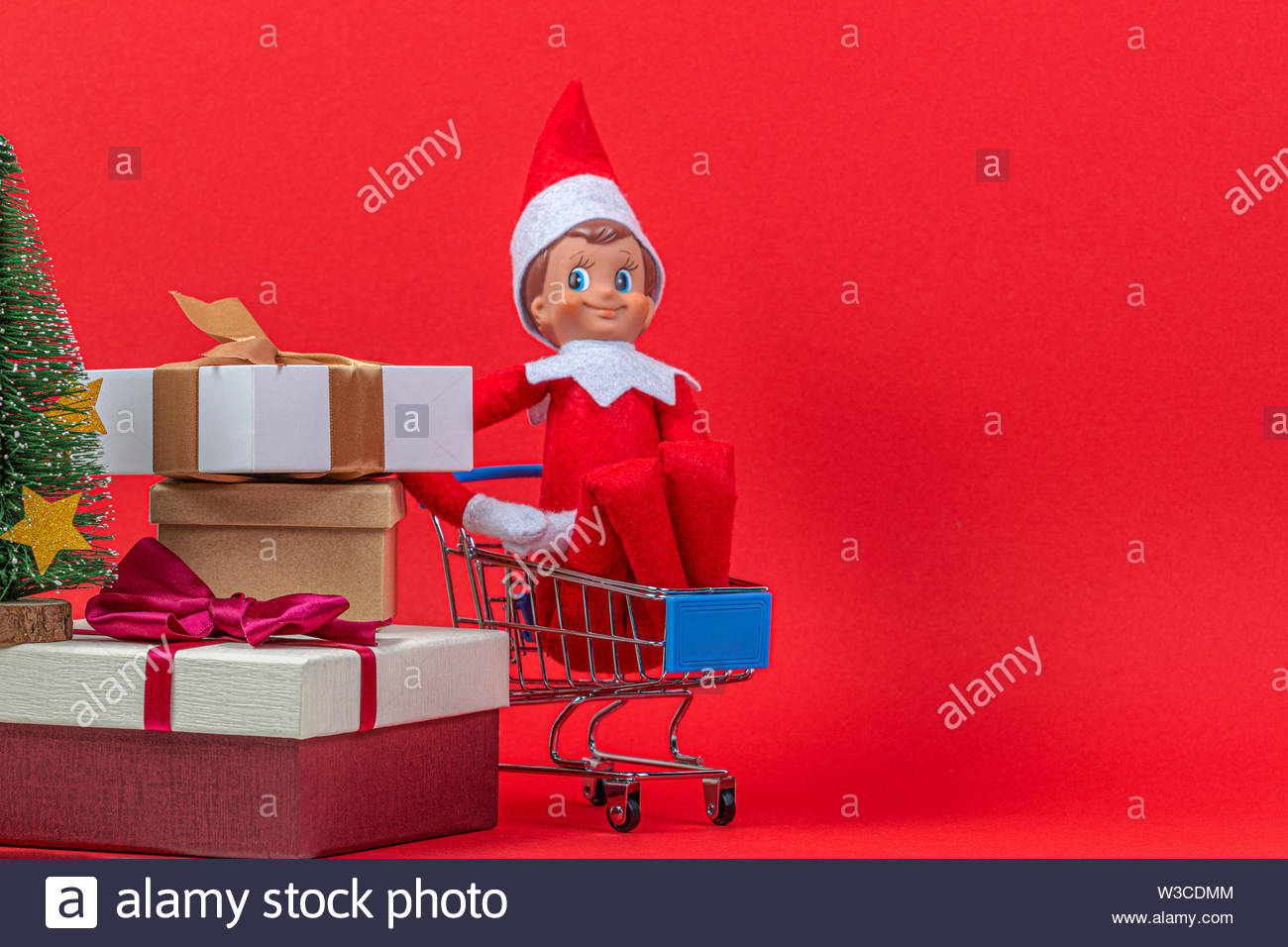 Christmas presents background. Christmas toy elf on shelf sitting in mini shopping cart on red background - Stock Image