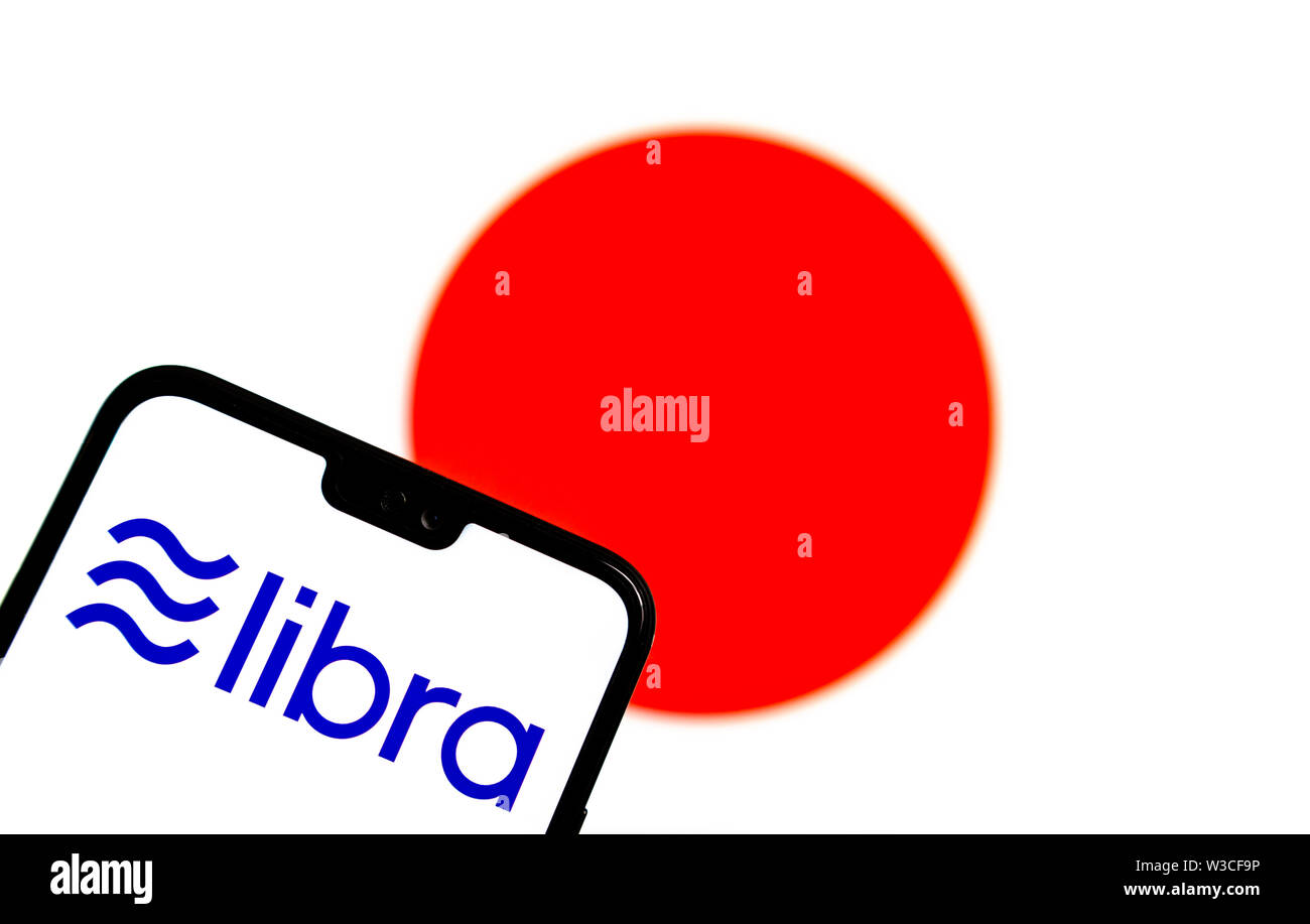 Facebook Libra crypto currency logo on the smartphone and blurred flag of  Japan at a laptop screen on the background. Conceptual photo. Stock Photo