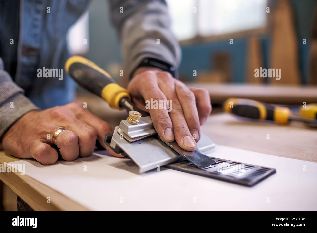 Carpenter sharpening a chisel close up view - Stock Image