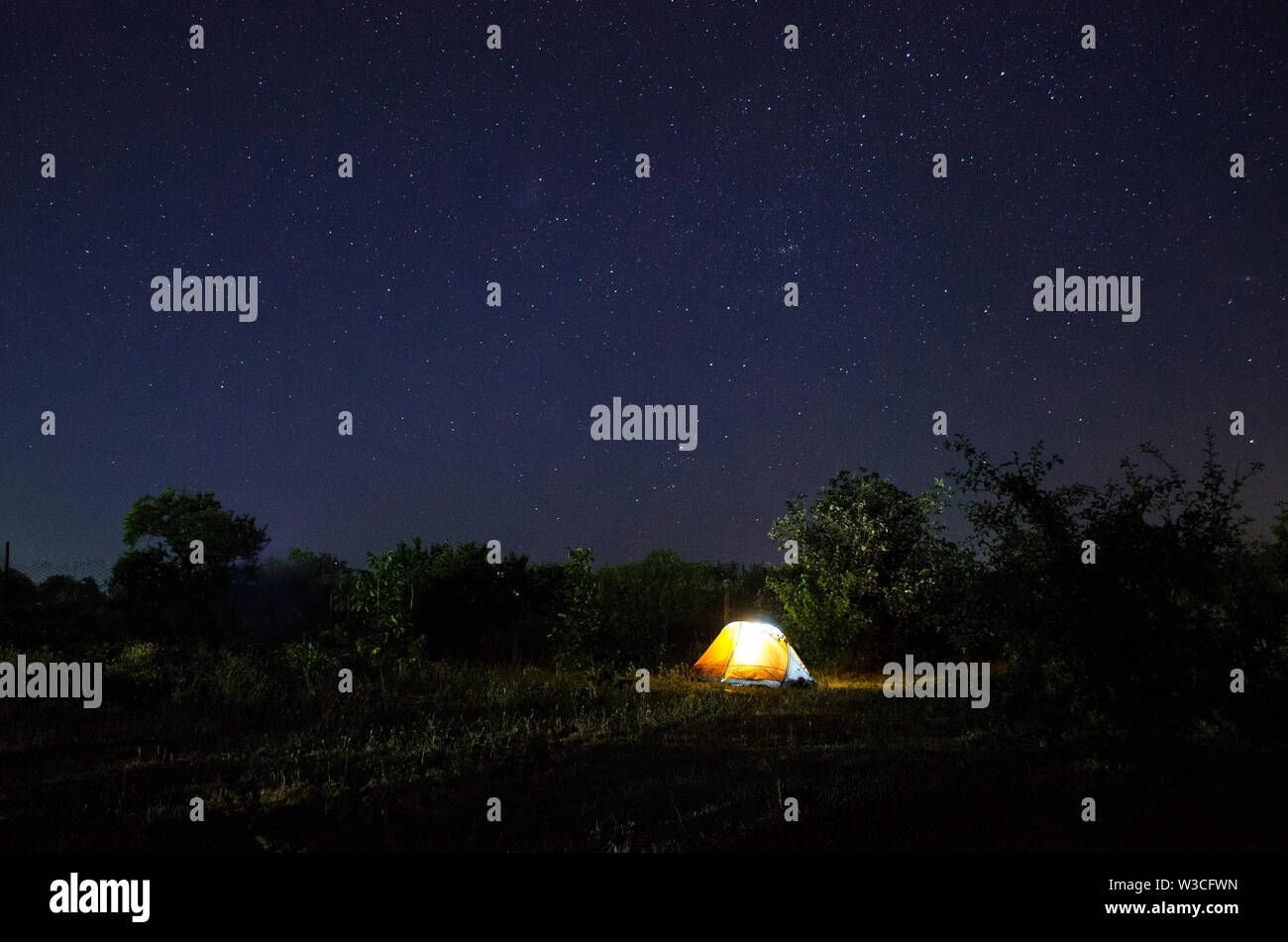 Camping tent under beautiful night sky full of stars. Starry night sky above illuminated touristic tent in the nature. - Stock Image