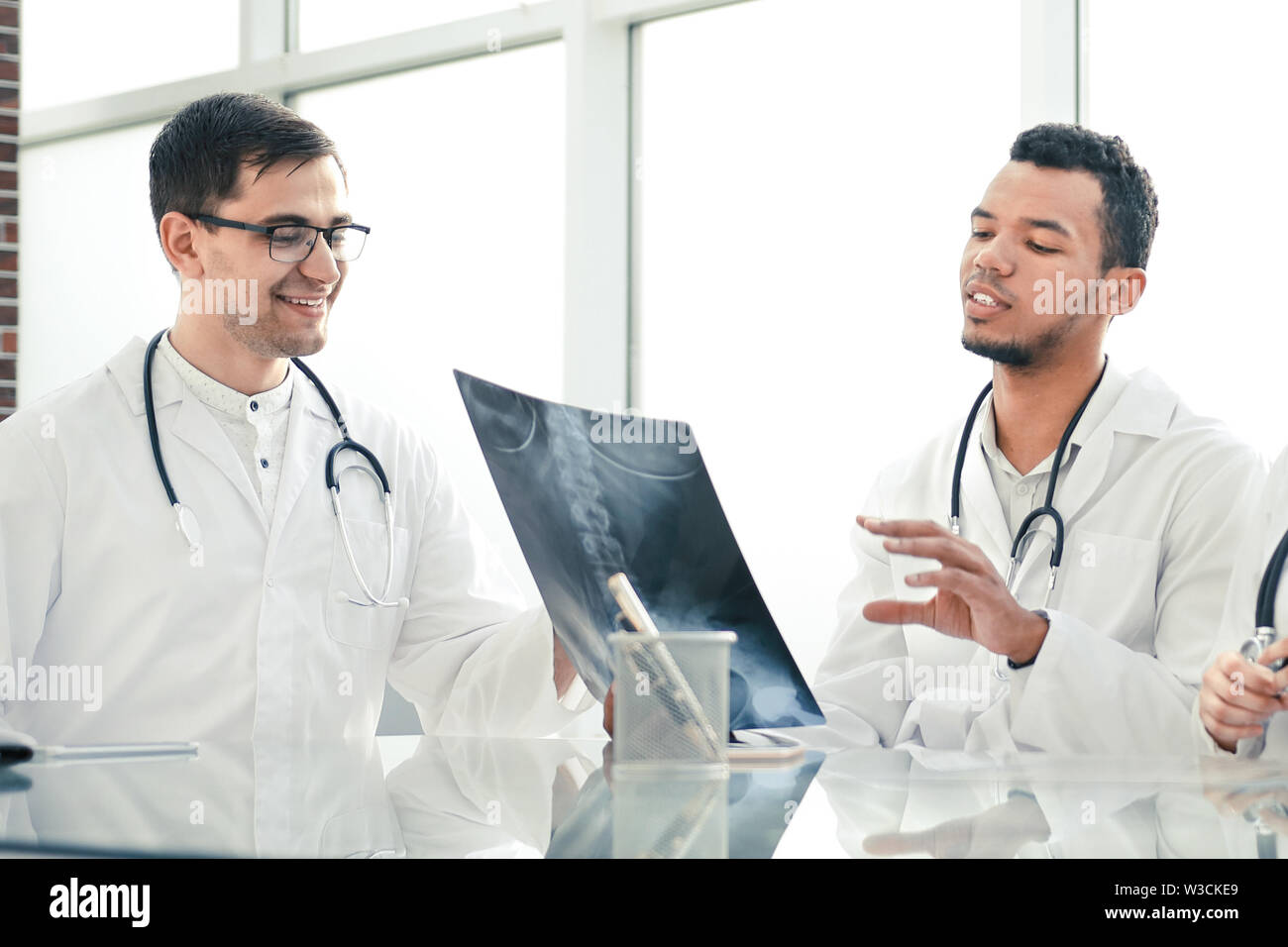 medical colleagues discuss x-ray, sitting at the office table. the concept of health - Stock Image