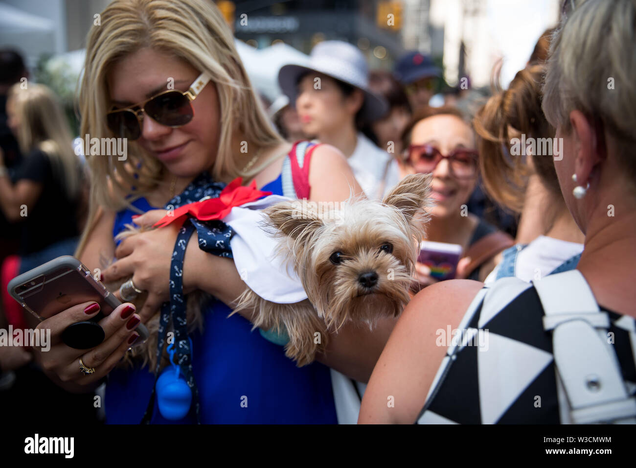 New York, USA. 14th July 2019. New York, French National Day. 14th July, 1789. A woman carrying a dressed dog attends the French Institute Alliance Francaise (FIAF)'s Bastille Day Celebration in New York, the United States, July 14, 2019. Bastille Day, also known as the French National Day, commemorates the start of the French Revolution and the storming of the Bastille in Paris on July 14, 1789. Credit: Michael Nagle/Xinhua/Alamy Live News - Stock Image