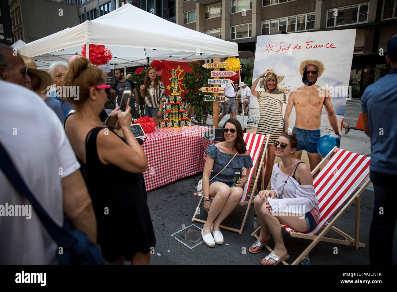 New York, USA. 14th July 2019. New York, French National Day. 14th July, 1789. People pose for photos with a cutout picture of a French beach during the French Institute Alliance Francaise (FIAF)'s Bastille Day Celebration in New York, the United States, July 14, 2019. Bastille Day, also known as the French National Day, commemorates the start of the French Revolution and the storming of the Bastille in Paris on July 14, 1789. Credit: Michael Nagle/Xinhua/Alamy Live News - Stock Image
