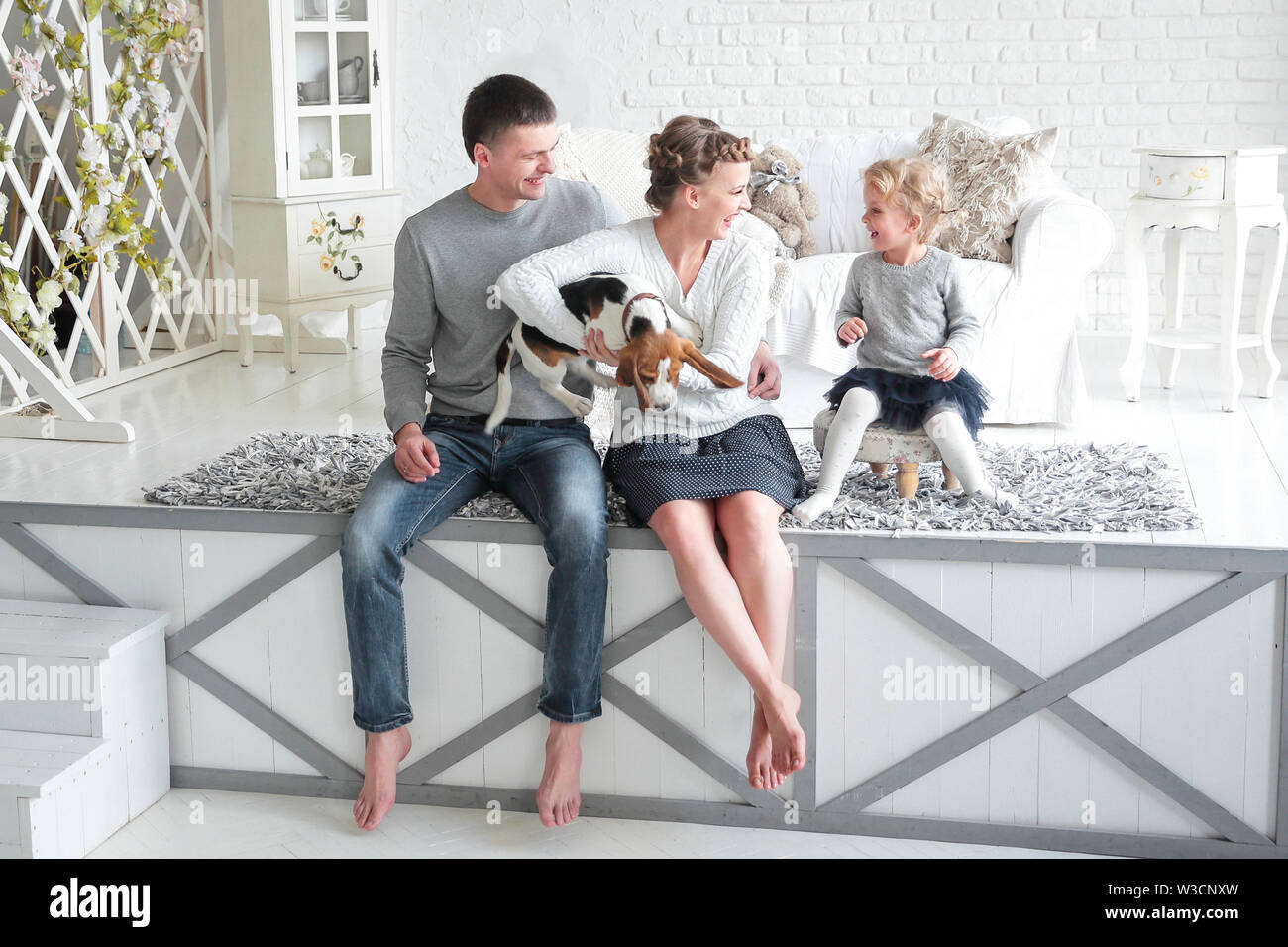parents and little girl playing with a dog on the bed in the bedroom. - Stock Image