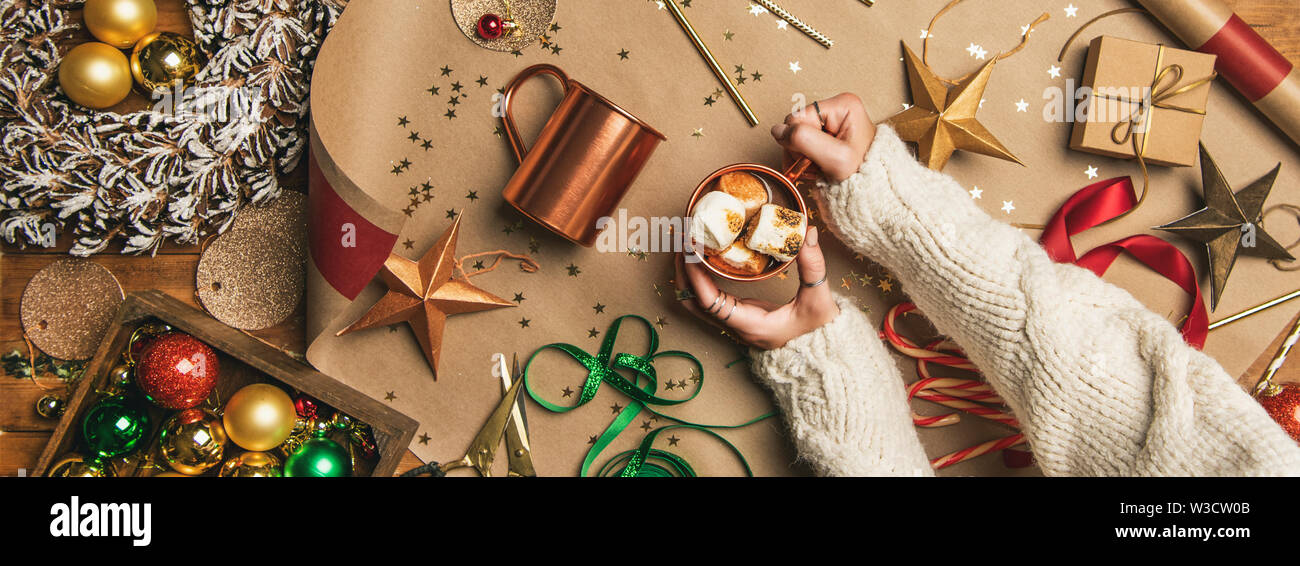 Hot chocolate in female hands and Christmas decoration, wide composition - Stock Image