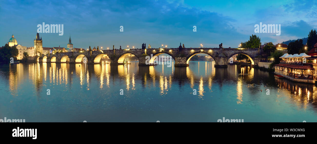 Panoramic image of illuminated Charles bridge in Prague in the evening - Stock Image