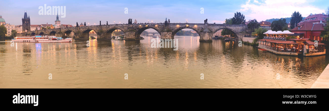 Panoramic image of Charles bridge in Prague early in the evening - Stock Image