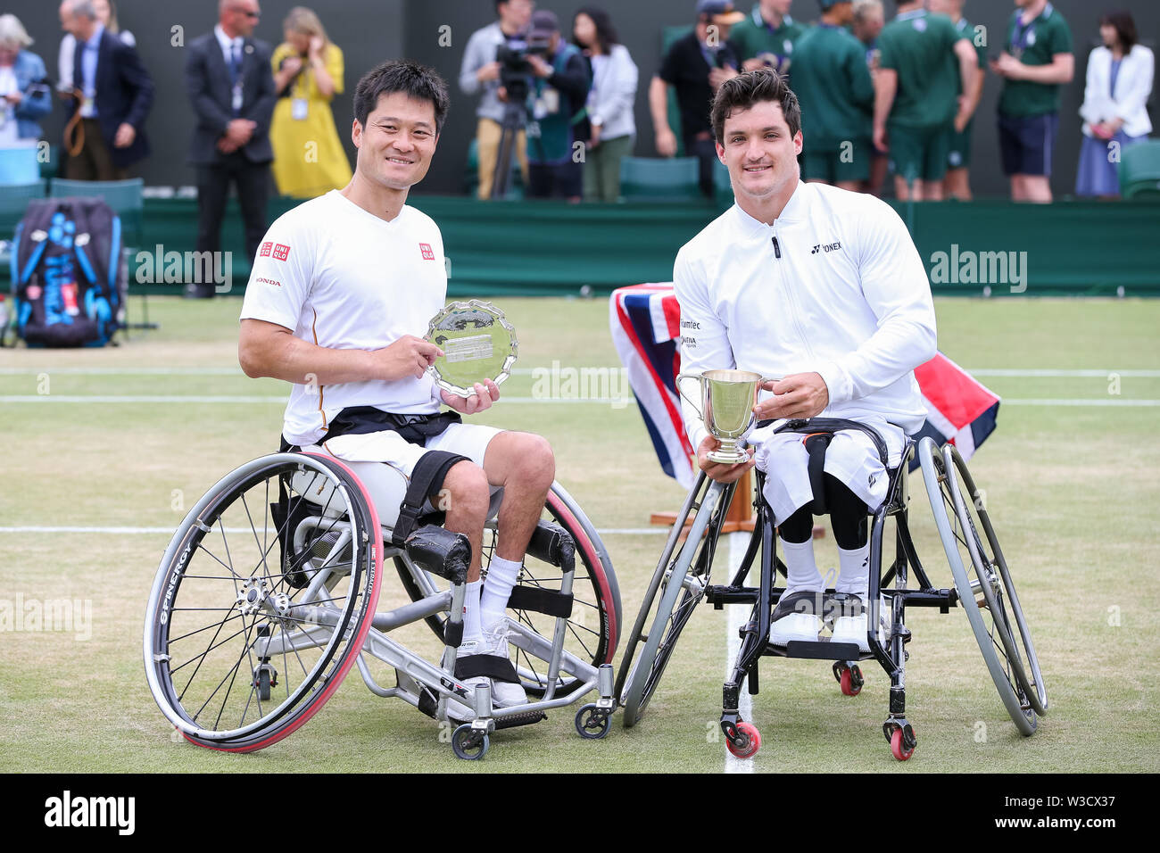 Wimbledon, London, UK. 14th July 2019. Shingo Kunieda of Japan and Gustavo Fernandez of Argentina pose with the trophy after the men's wheelchair singles final match of the Wimbledon Lawn Tennis Championships at the All England Lawn Tennis and Croquet Club in London, England on July 14, 2019. Credit: AFLO/Alamy Live News - Stock Image