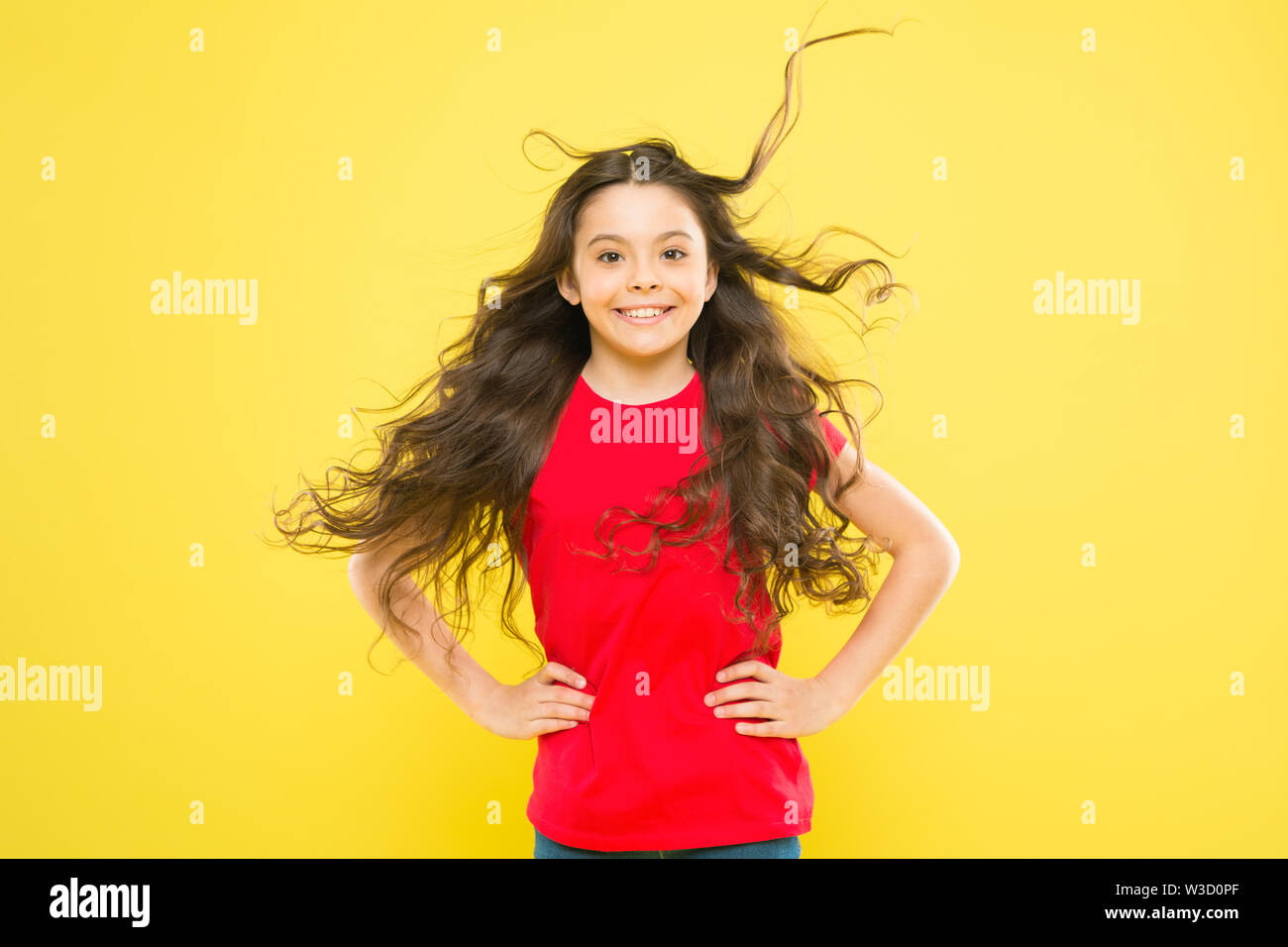 Interested in my hair and my hairdresser. Happy small girl child smiling with flowing long brunette hair on yellow background. Kids hairdresser. Hairdresser salon. - Stock Image