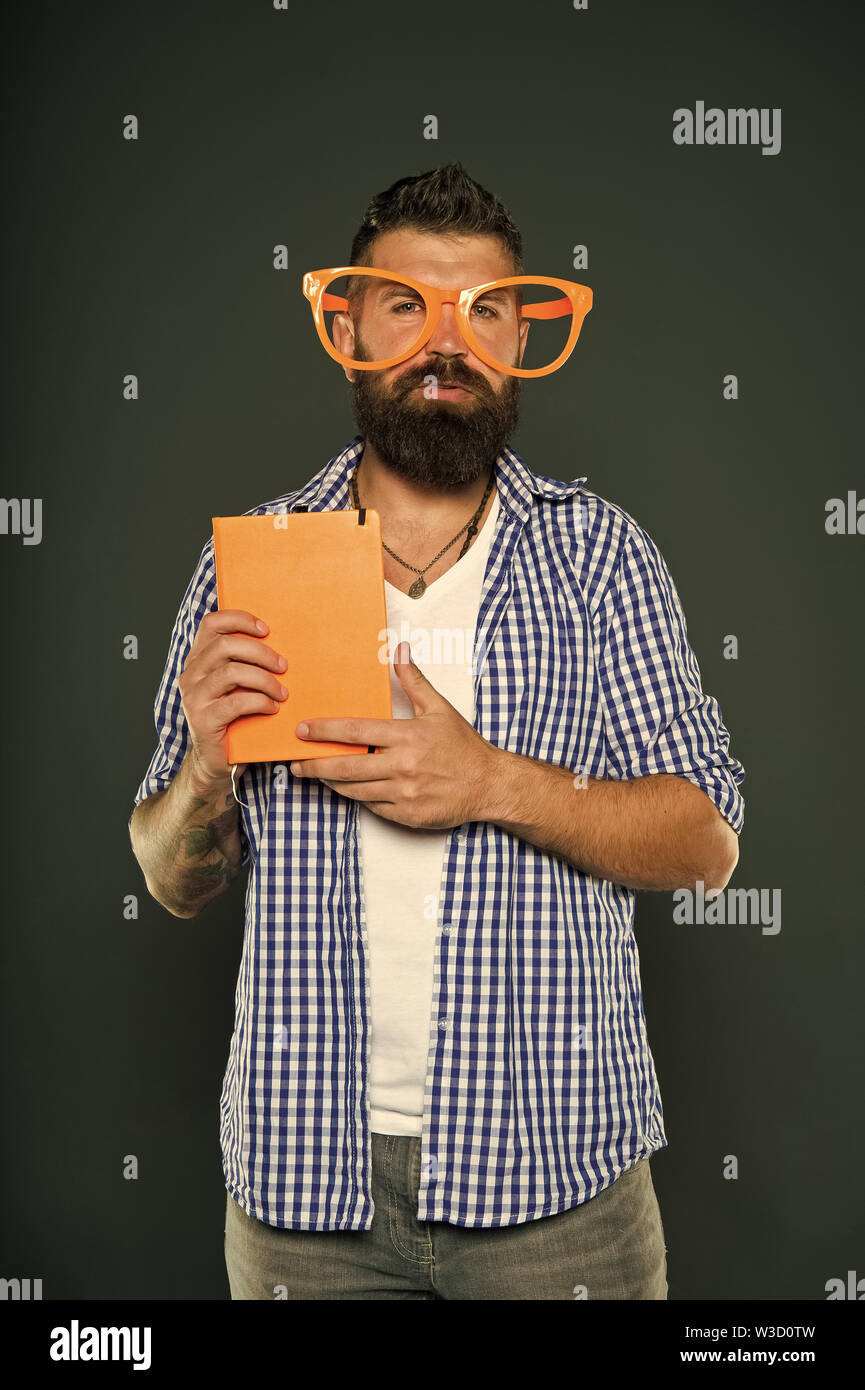 Nerd is the new cool. Study nerd holding book. Book nerd wearing fancy glasses. University male student with lecture notes. Bearded man in party glasses with lesson book. - Stock Image