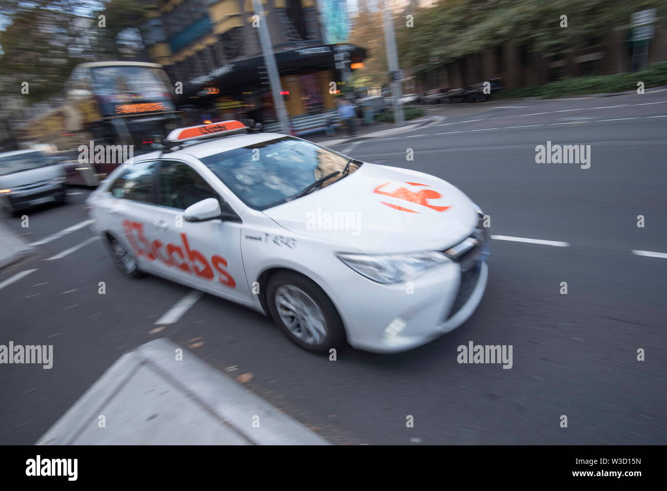 A blurred image of a moving Sydney taxi driving in a turning lane in the city near Central Station - Stock Image
