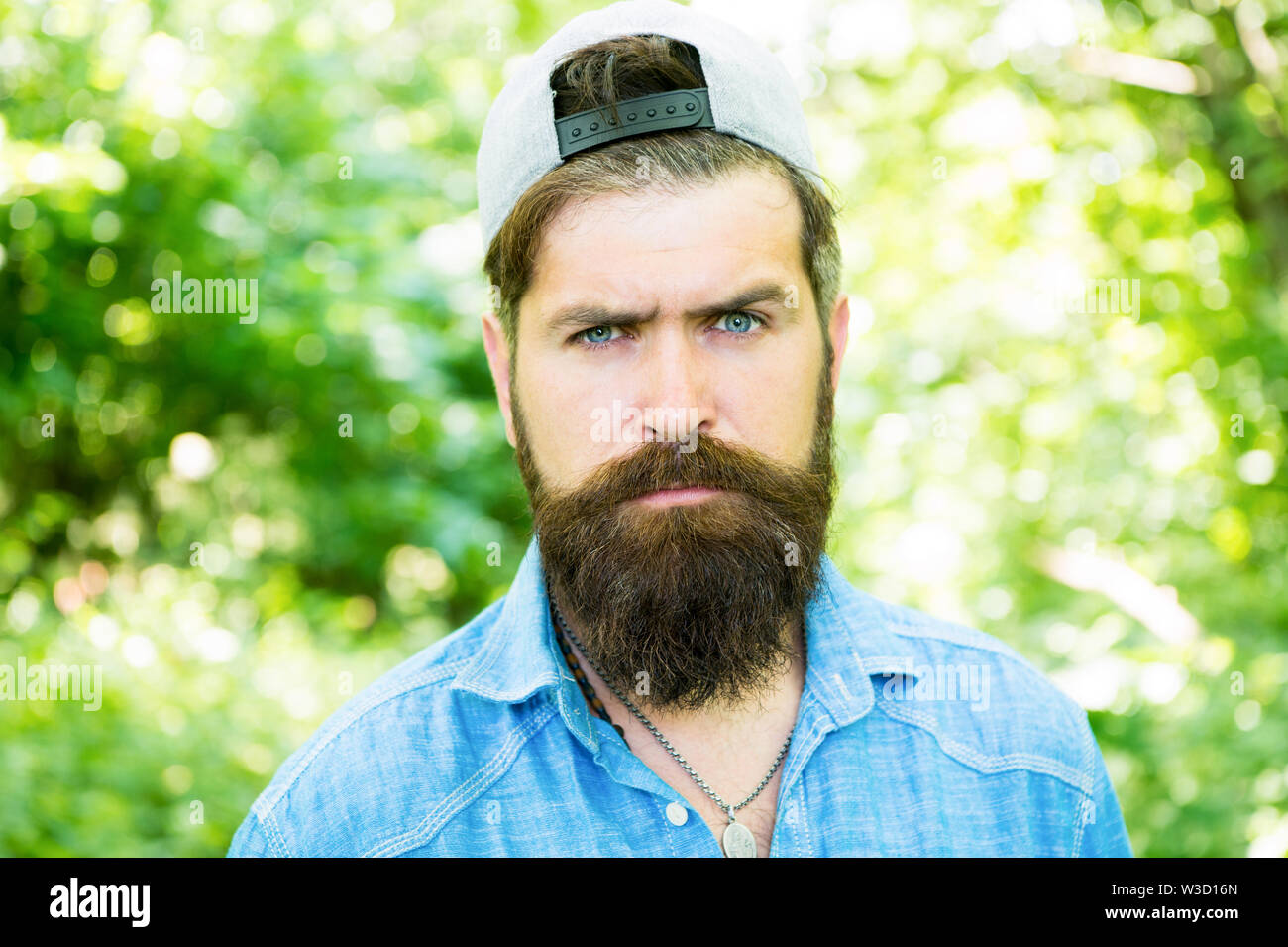 serious bearded man. Mature hipster with beard. male facial care. brutal man with beard. barber. hispter style. Fashion portrait of man. Hair beard care. guy in wood. summer camping. Indulge yourself. Stock Photo