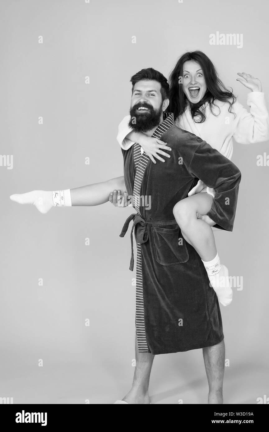 Happy family. Perfect morning. Having fun. woman and bearded man in robe. romantinc couple in love. man hipster love his woman. smiling woman hug man. man in robe hold woman in hands. Happy together. - Stock Image