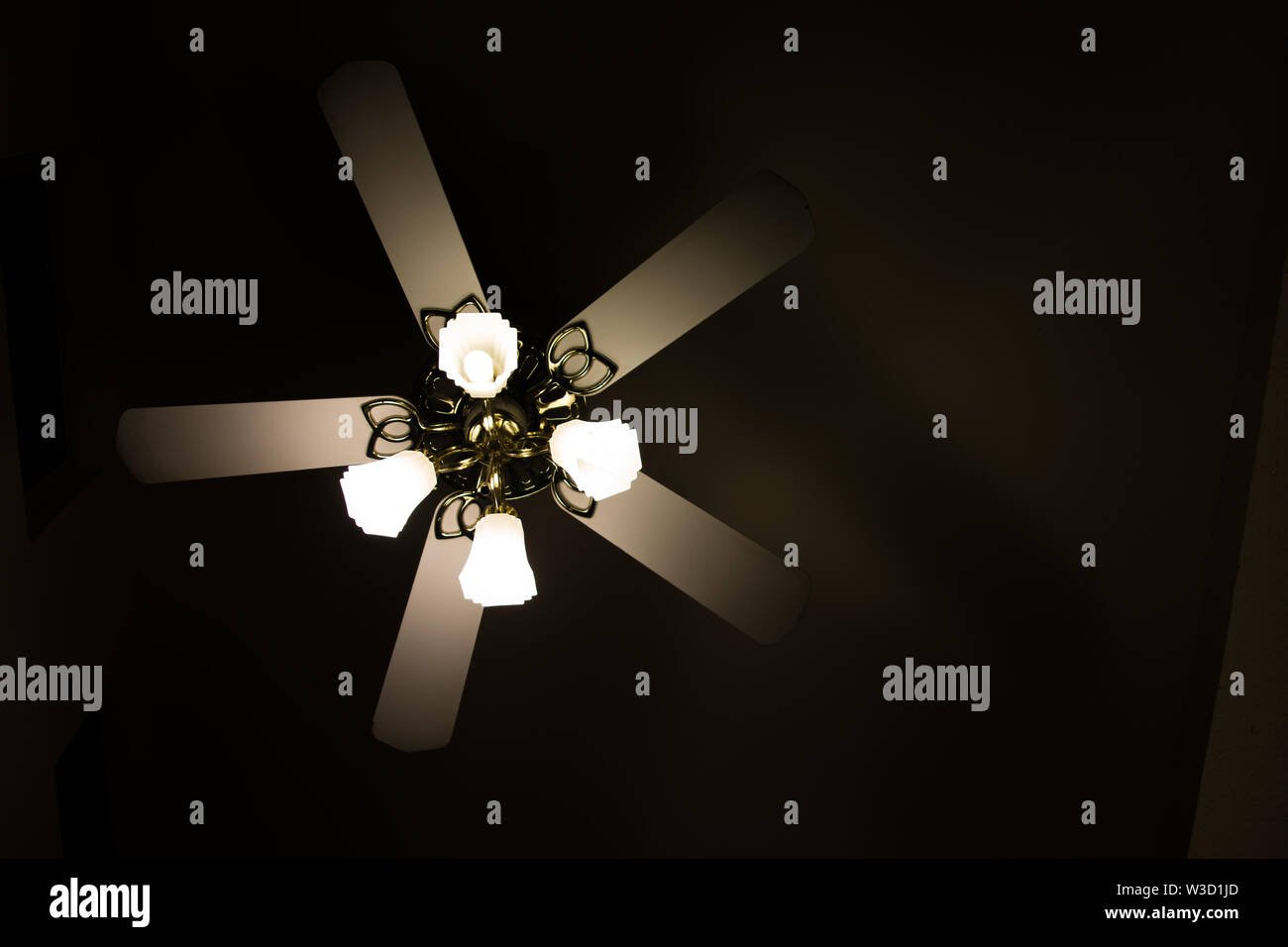 Ceiling fan with lights in the dark. - Stock Image