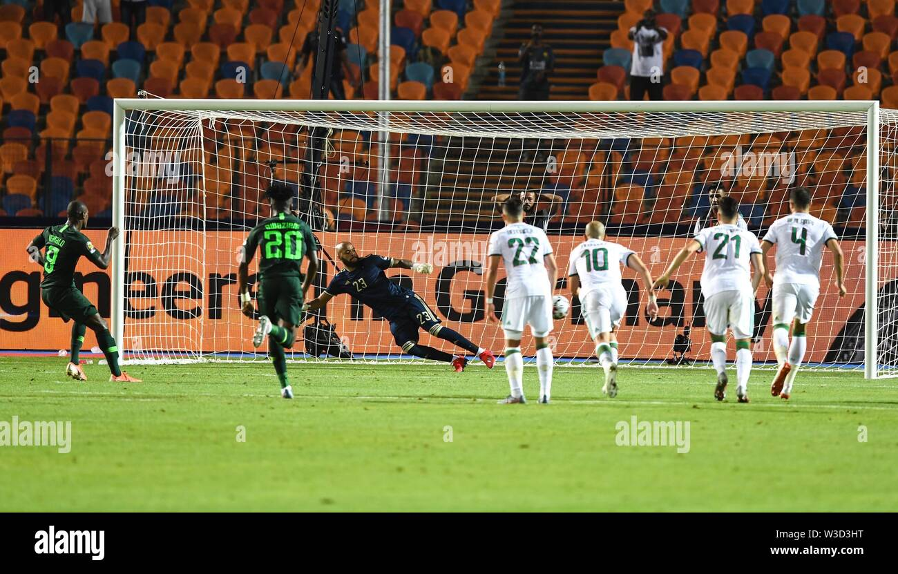 Cairo. 14th July, 2019. Odion Ighalo of Nigeria shoots to score from the penalty spot during the semifinal match between Algeria and Nigeria at the 2019 Africa Cup of Nations in Cairo, Egypt on July 14, 2019. Credit: Li Yan/Xinhua/Alamy Live News - Stock Image