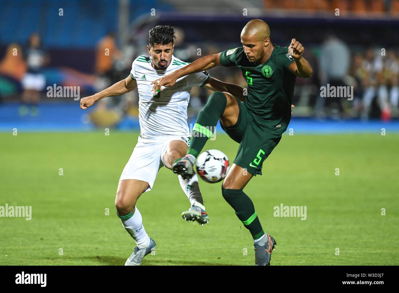 Cairo. 14th July, 2019. Baghdad Bounedjah of Algeria (L) competes with William Ekon of Nigeria during the semifinal match between Algeria and Nigeria at the 2019 Africa Cup of Nations in Cairo, Egypt on July 14, 2019. Credit: Li Yan/Xinhua/Alamy Live News - Stock Image
