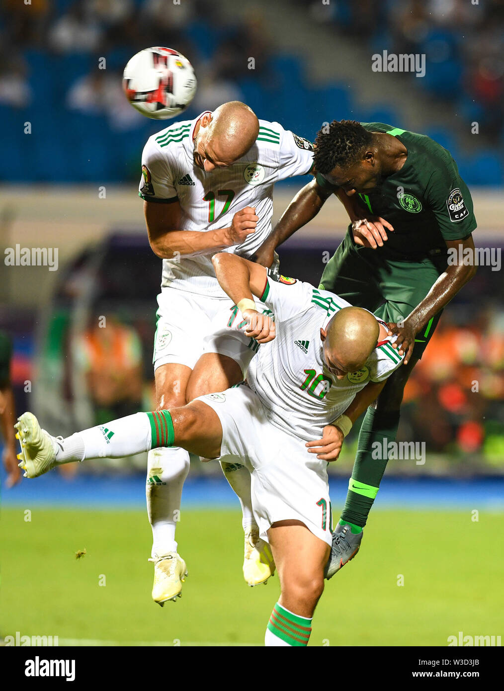 Cairo, Nigeria during the semifinal match between Algeria and Nigeria at the 2019 Africa Cup of Nations in Cairo. 14th July, 2019. Sofiane Feghouli (down) and Adlane Guedioura (L, up) of Algeria compete with Wilfred Ndidi (R, up) of Nigeria during the semifinal match between Algeria and Nigeria at the 2019 Africa Cup of Nations in Cairo, Egypt on July 14, 2019. Credit: Li Yan/Xinhua/Alamy Live News - Stock Image