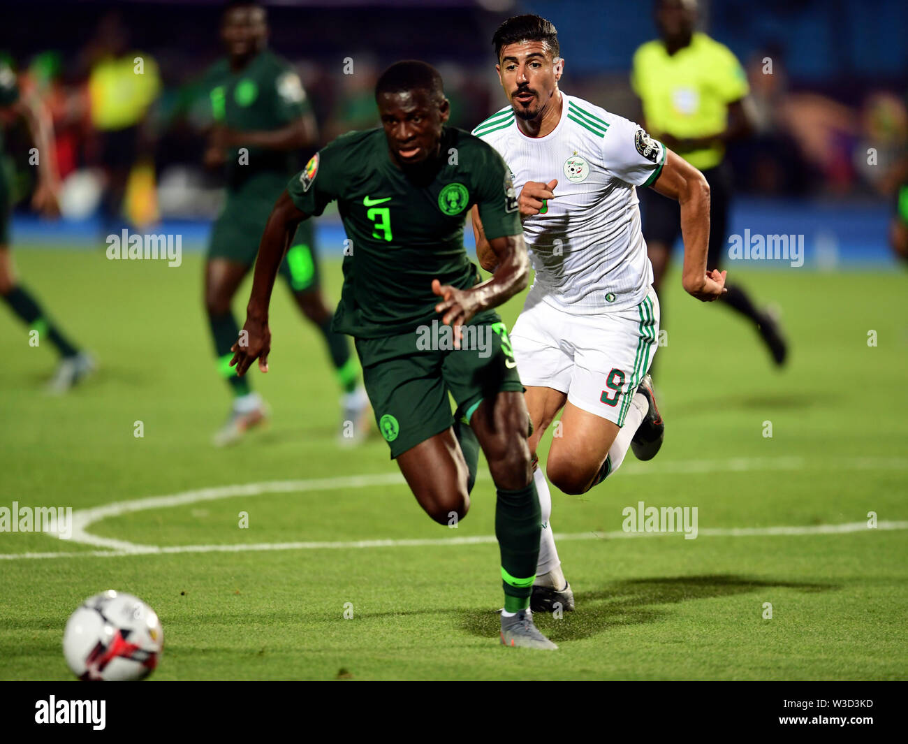 Cairo. 14th July, 2019. Baghdad Boudedjah (R) of Algeria vies with Jamilu Collins of Nigeria during the semifinal match between Algeria and Nigeria at the 2019 Africa Cup of Nations in Cairo, Egypt on July 14, 2019. Credit: Wu Huiwo/Xinhua/Alamy Live News - Stock Image