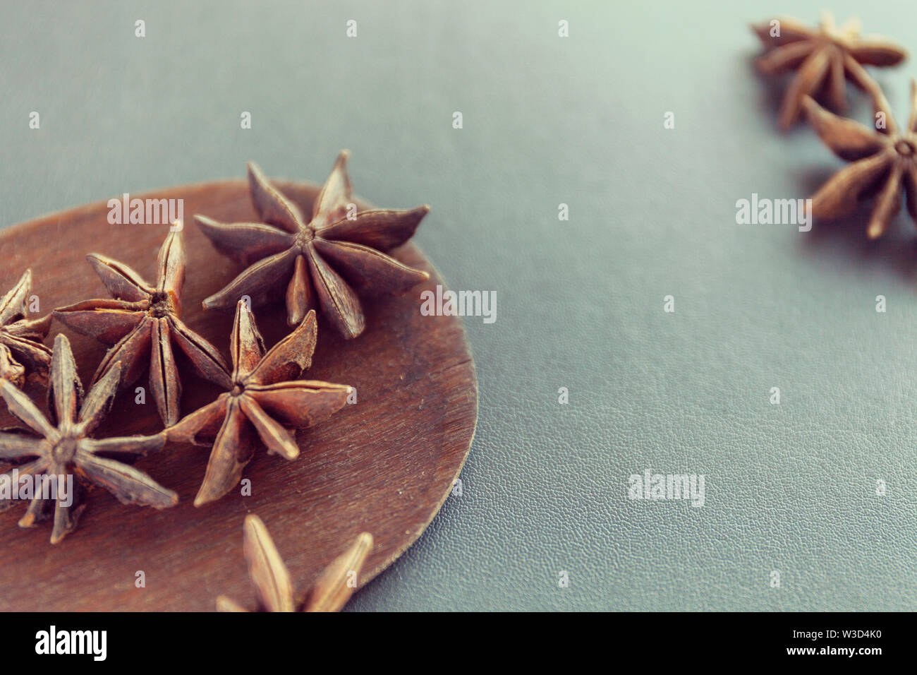 Dry Star anise on a brown wooden spatula. Natural food spices and seasonings. Tasty eating. Close-up. Stock Photo