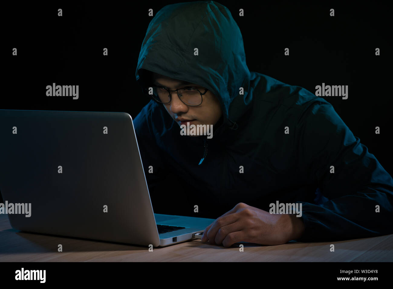 Computer hacker working in dark room - Stock Image