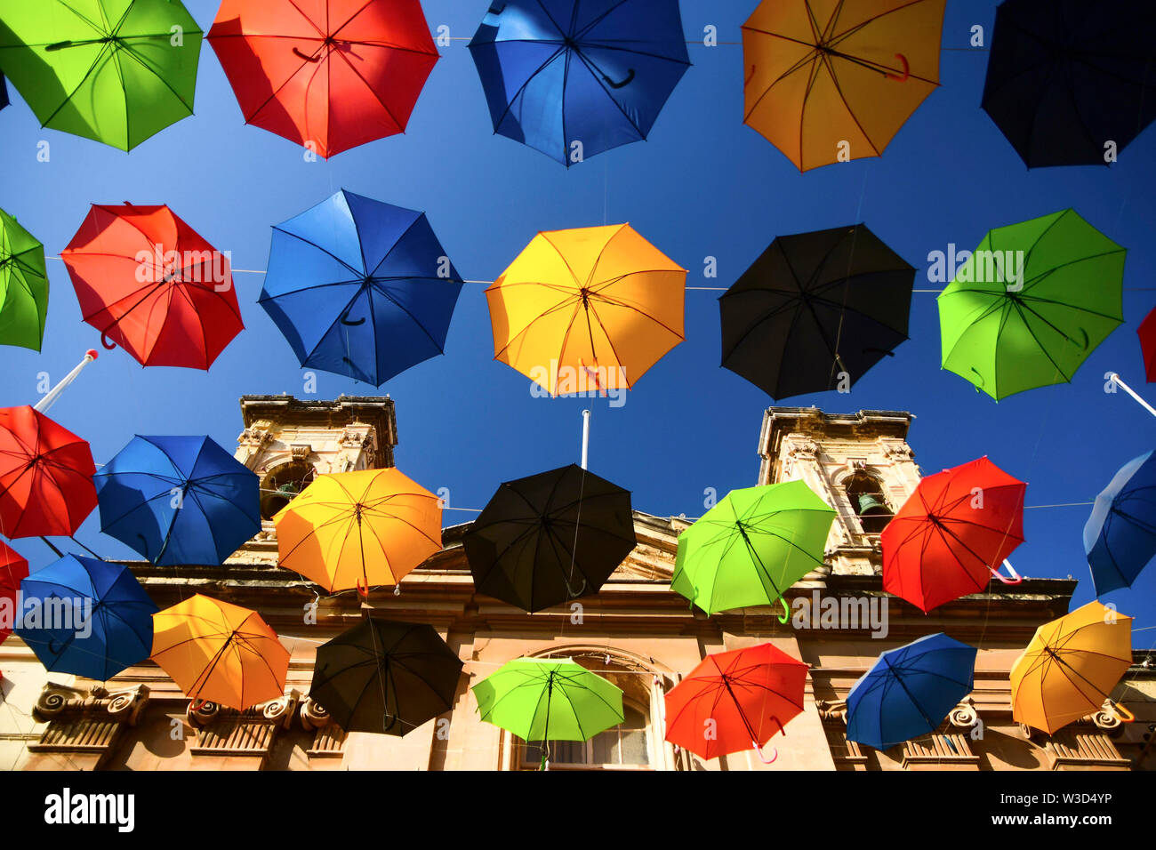 Beijing, China. 13th July, 2019. Photo taken on July 13, 2019 shows umbrellas suspended in the air along a street to bring back the popular 'Umbrella Street' spectacle in Zabbar, Malta. Credit: Jonathan Borg/Xinhua/Alamy Live News - Stock Image