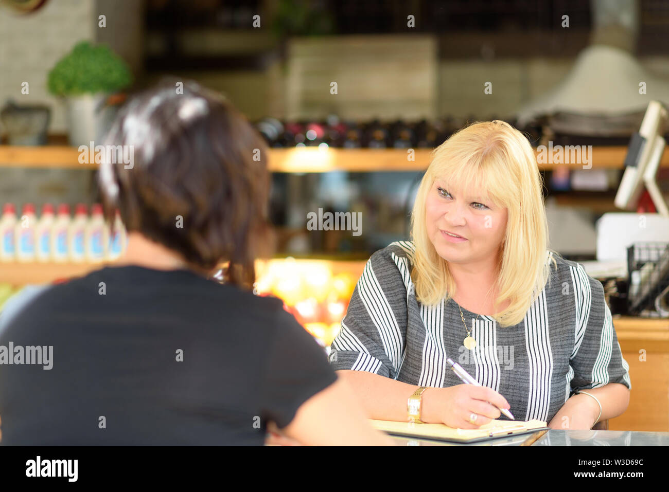 Young depressed woman talking to psychologist during session,mental health.Psychologist with patient in cafe. Portrait of middle aged woman profession - Stock Image