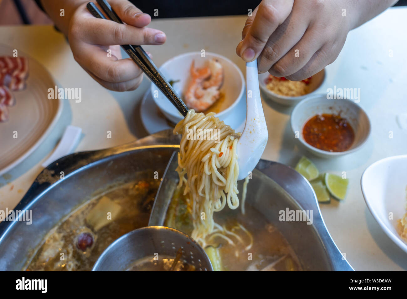 Woman using chopsticks to pick noodles in Chinese hotpot - Stock Image