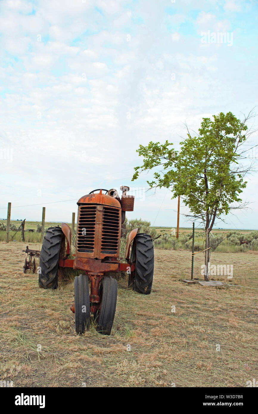 This old antique tractor has seen better days. - Stock Image