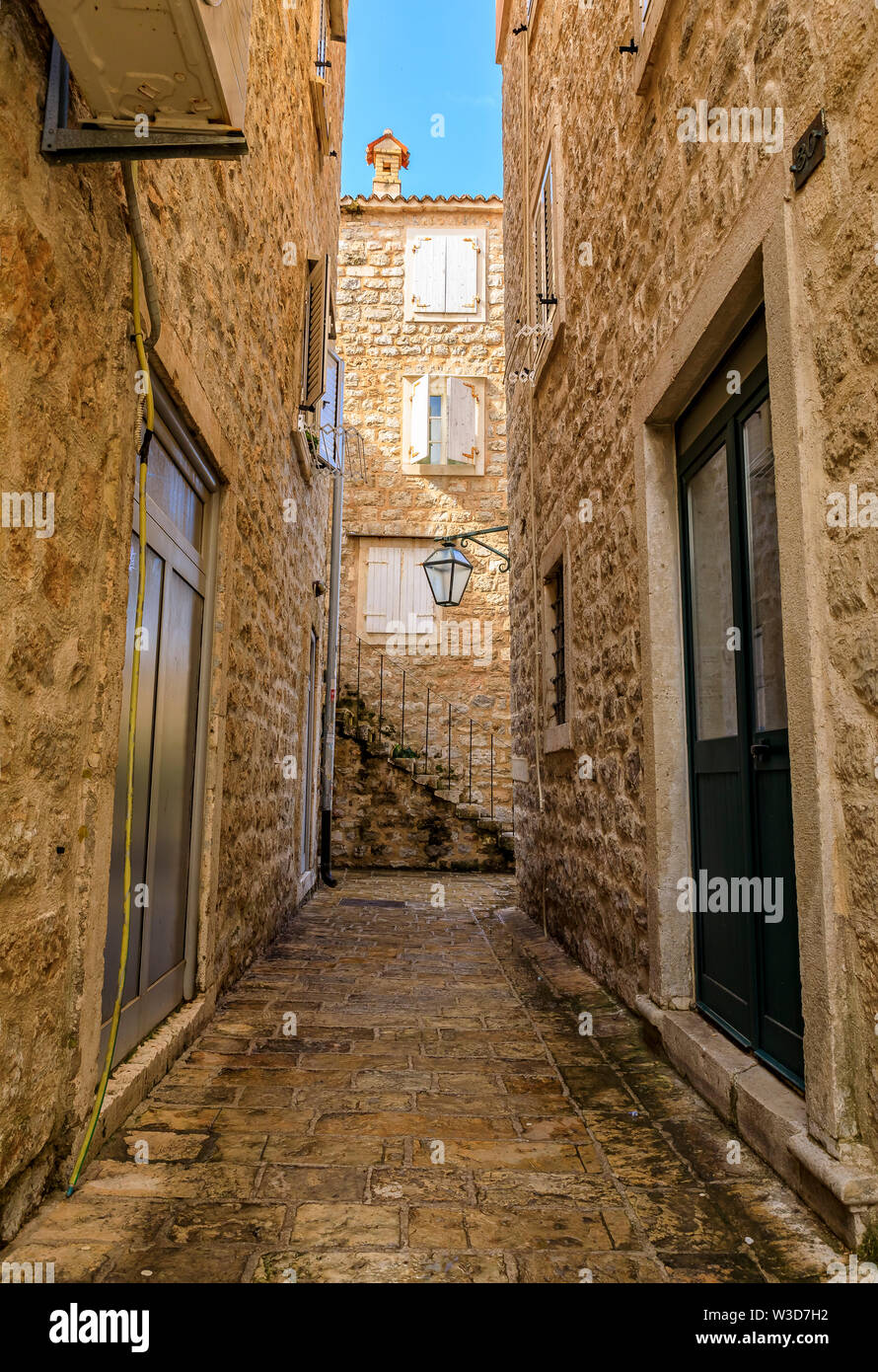 Picturesque narrow streets of the well preserved medieval Old town with shops, cafes and restaurants in Budva, Montenegro in the Balkans - Stock Image