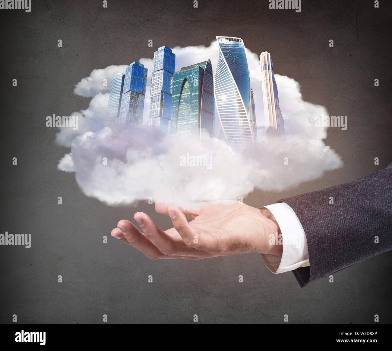 Business hand holds skyskrappers on outstretched hand. Over gray background. - Stock Image