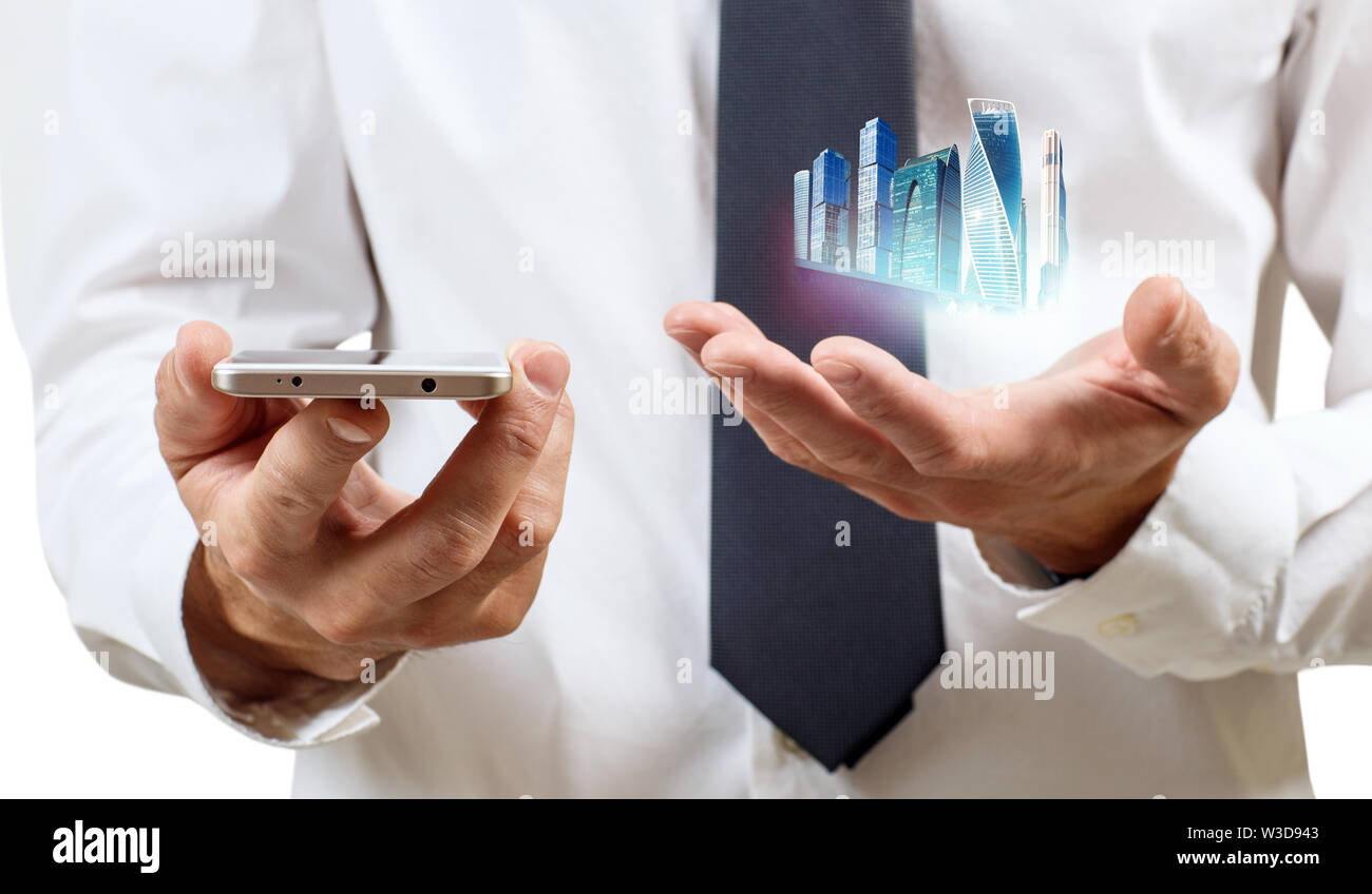 Businessman holds skyskrappers on outstretched hand and smartphone. Over white background. - Stock Image
